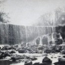 Photo:Meg Haig standing (left) at the foot of the Limefield Falls, re-modelled by James Young as a miniature Victoria Falls in honour of his friend, David Livingstone.  c.1917.