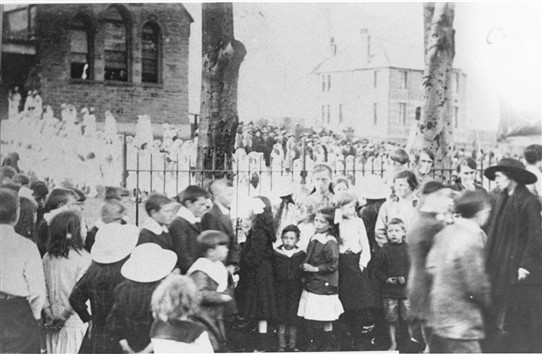 Photo:The May Procession gathers in front of the Catholic School.  In the background the Chapel House, but as yet no Chapel. This dates the photo to the early 1920s..