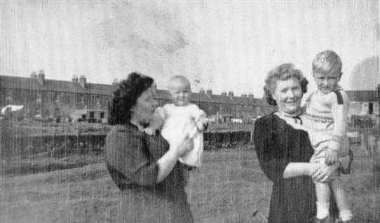 Photo:Margaret (left) and Betty Hamilton with a friend's children, Susanne and John Dunleavy.  Taken in front of Addiewell Pond.  In the background, Livingstone Street.  1950s.